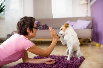 Frau spielt mit Hund im Wohnzimmer