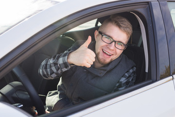 Cheerful casual guy smiling happily showing thumbs up sitting in a big white car