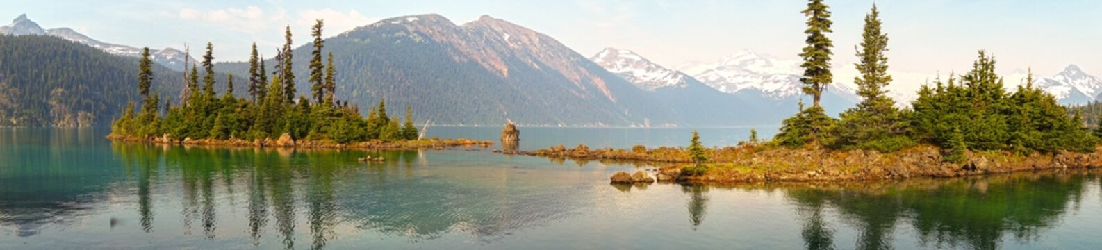 Garibaldi Lake Wide Panoramic Landscapewith distant snowy mountain peaks obscured by smoke from summer wildfires