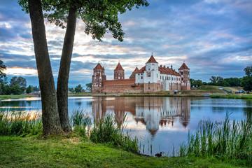 Mir Castle reflecting in water in the evening, Belarus