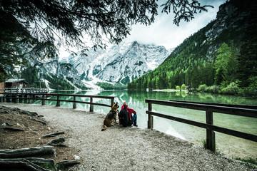 Active man and dog looking at Pragser Wildsee or Braies Lake