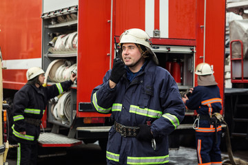 Fireman (firefighter) in action standing  near a firetruck. Emergency safety. Protection, rescue from danger.