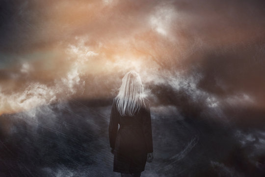 Grunge dramatic dark stormy sky with woman walking. Double exposure effect used.