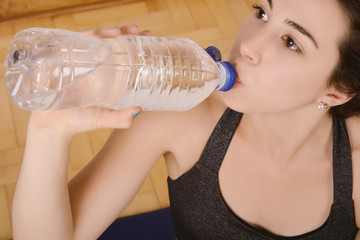 Close up view of sporty woman drinking water