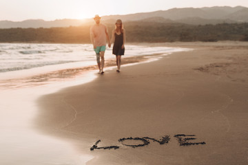 word Love on the sand coast and blurred loving couple on background walking on empty beach at sunset