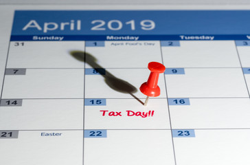 Red pushpin in calendar on April 15th for tax day