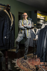 Owner of bespoke fashion clothing shop in New York City standing and smiling at camera