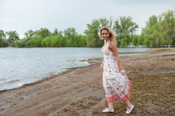 Blonde strolls in a long dress on the shore of the lake
