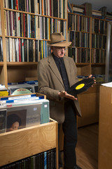 Owner of neighborhood record shop in New York City holding and looking at LPs inside the store