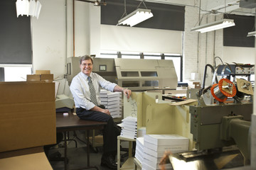 Business owner sitting at desk with printed material around him inside an office in New York City, USA