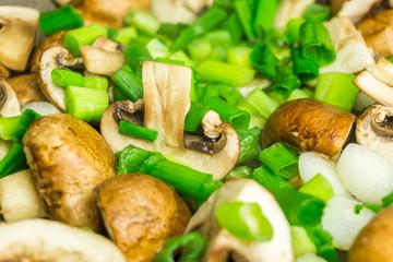 Pilze mit grünen Lauchzwiebeln in der Pfanne