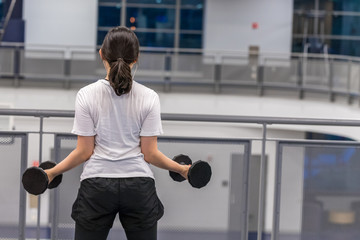 A standing female athlete stretching with dumbbells