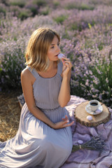 attractive woman eating macaron in violet lavender field