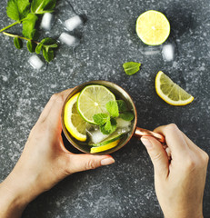Woman's hands  holding a copper mug of lemonade with fresh mint