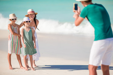 Family of four taking a selfie photo on their beach holidays.