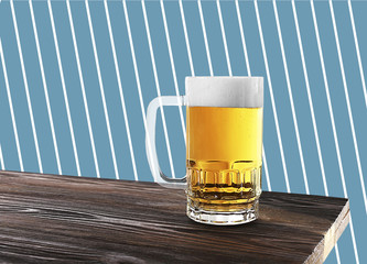 Glass mug of beer on wooden table against patterned background