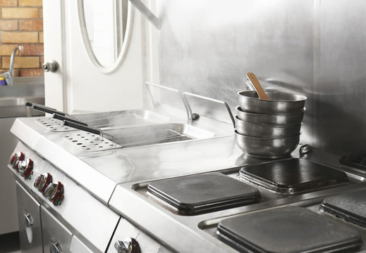 Professional equipment with cookware in restaurant kitchen