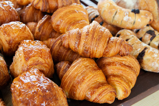 Assortment of delicious and buttery croissants made by pastry chef. All look very tasty and delightful. Natural light.