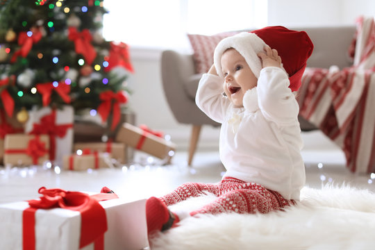 Cute baby in Santa hat on floor at home. Christmas celebration