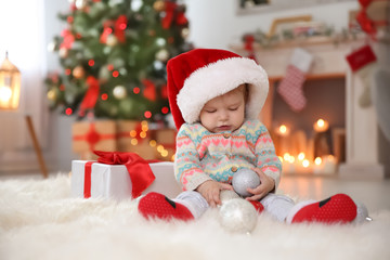 Cute little baby in Santa hat sitting on fur rug at home. Christmas celebration