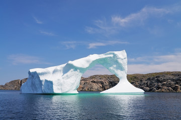 Iceberg in front of a rocky island, Newfoundland and Labrador