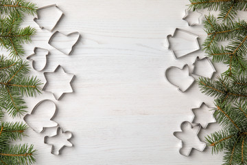 Flat lay composition with cutters for Christmas cookies on wooden background