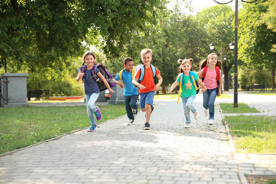 Cute little children with backpacks running outdoors. Elementary school