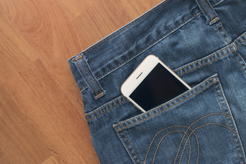 Smart phone and jeans on wooden floor