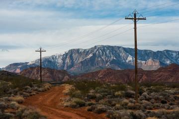 Dirt road and telephone poles through the mountainous desert, Southern Utah