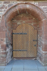 ancient wooden door in the brick wall of the knight's castle