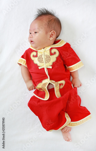 Infant Baby Boy In Cheongsam Lying On White Fur Background During