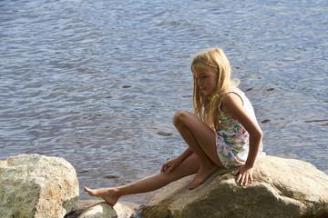 Child girl having fun on rock on the beach in summer