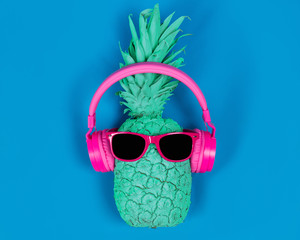 Pineapple in pink headphones and glasses on a blue background