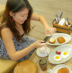 young pretty and happy Asian Korean travel blogger woman taking picture with mobile phone of beautiful breakfast table at outdoors coffee shop smiling