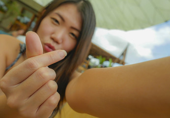 happy Asian Korean tourist woman smiling holding mobile phone or camera taking self portrait selfie picture outdoors doing love fingers heart sign