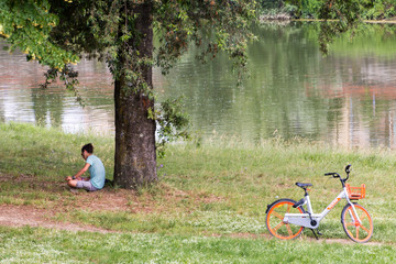 Young man with bicycle relaxing in park by the river