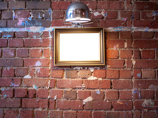 Mock up blank wooden picture frame hanging on grungy old red brick wall with spotlight above. Vintage style artwork, painting or picture background template in room.