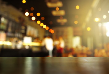 top of wood table with light of blur pub or bar in the dark night background