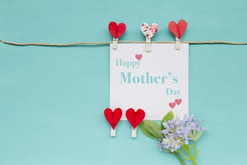 Happy Mother's day  card with red heart clip and flower on blue texture background, greeting card concept