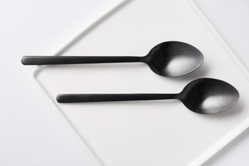 top view of two spoons and plate on white table, minimalistic concept