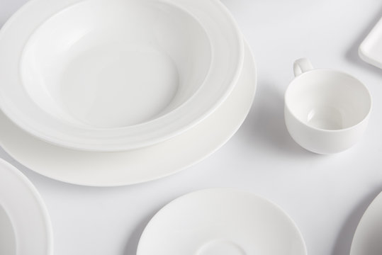 selective focus of different plates and cup on white table