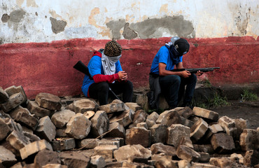 Pro-government supporters sit in a barricade after clashes with demonstrators in the indigenous community of Monimbo