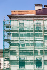 metal scaffolding with green safety net near building facade