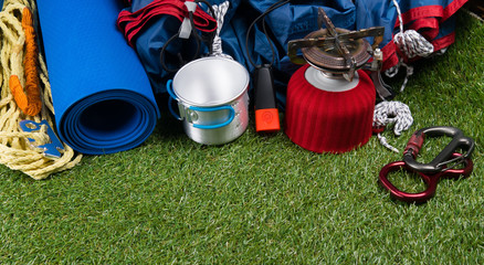 green background of the lawn. travel kit for outdoor activities, tent, gas burner, mug carbines, and rope, and blue Mat