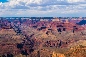 View of Grand Canyon from the South Rim; Brilliant colors of the rocky north wall are seen; blue sky and clouds are overhead.
