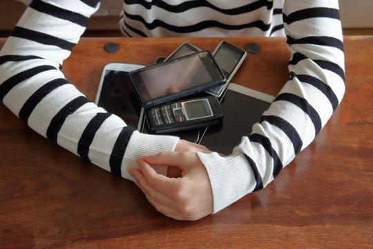 Ręce dziewczynki obejmują stos telefonów komórkowych, smartfonów leżących na drewnianym stole