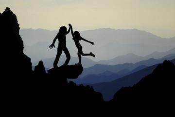 Teamwork couple celebrating in inspiring mountains sunset