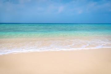 Sea water splashing on the brown sand