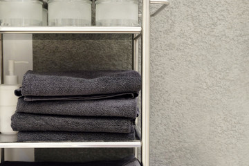 Folded towels, carpet slippers and bathrobes on a shelf of a closet in a hotel Wall mural