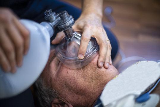 rianimazione cardiopolmonare con pallone e massaggio cardiaco su anziano svenuto a seguito di arresto cardiaco in un parco